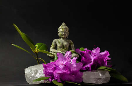 Beautiful pink rhododendron flower decorated with rock crystal and Buddha statue
