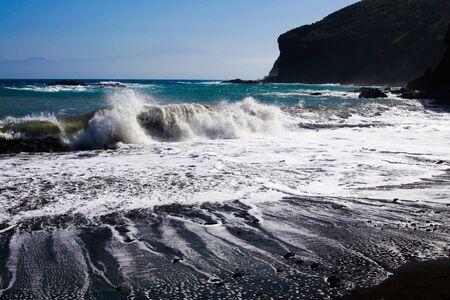 Powerful white foaming waves hit black lava sand beach in the evening sun - Vallehermosa, La Gomera, Canary Islands