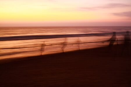 Long time exposure: Ghostly silhouettes of blurred fishermen catch up their net during sunset on beach, Sri Lanka