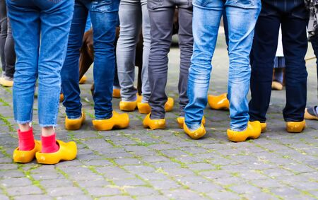 Close up of blue jeans legs of group of people wearing traditional wooden clogs during guided city tour - Xanten, Germany