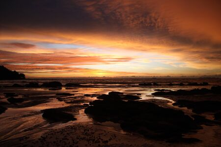 Sky with deep hanging storm clouds and wet sludge during low tide swathed in yellow and red bright light during sunset on tropical island Ko Lanta, Thailand