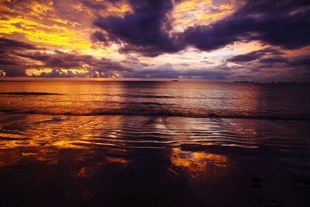 Burning sky and sea during sunset over the ocean of tropical island Ko Lanta, Andaman Sea, Thailand