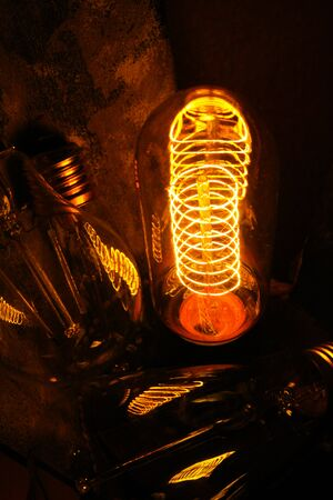 Cobbled classic incandescent Edison light bulbs with visible glowing wires in the night