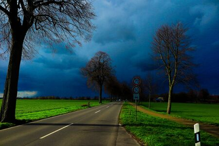 VIERSEN, GERMANY - Dark sky with hail bearing clouds over country road and trees announcing thunder storm. Sun and dark clouds causing extreme bright lighting conditions.
