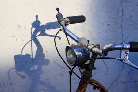 Handlebars of old rusty bike throwing shadows on white wall
