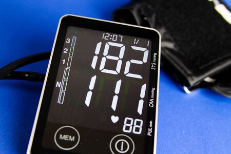 Close up of digital sphygmomanometer monitor with cuff showing high diastolic and systolic blood pressure
