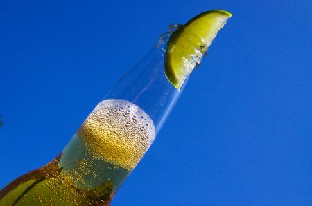 Close up of isolated bottleneck with sparkling yellow beer and a slice of lime against cloudless deep blue sky