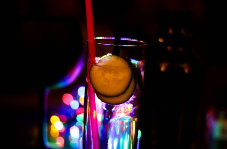 Close up of isolated gin tonic cocktail glass with slices of cucumber and pink plastic straw. Vibrant colorful bokeh and blurred bottle background. Banque d'images