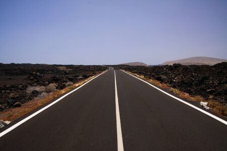 Lanzarote - Timanfaya NP: Driving trip on endless empty asphalt road between black lava rocks in barren landscape into endlessness