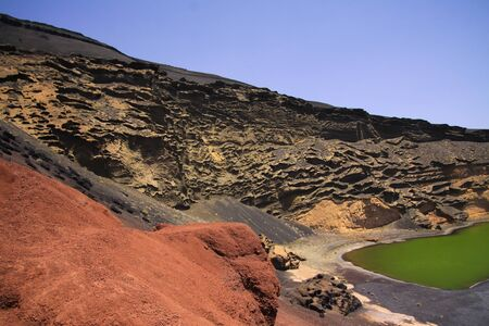 View on secluded deep green lake (Lago verde) in lagoon surrounded by impressive cliffs - El Golfo, Lanzarote