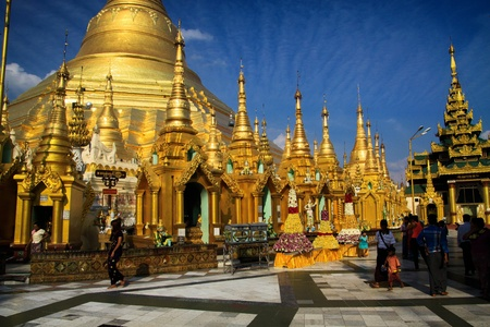 YANGON, MYANMAR - DECEMBER 30. 2015: View over square on golden stupas and dome of gold pagoda against blue sky - Shwedagon pagoda