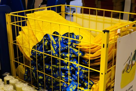 Kaarst, Germany - November 16. 2019: View on metal box with yellow shopping bags in Swedish furniture store IKEA.