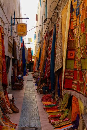 ESSAOUIRA, MOROCCO - SEPTEMBER 29. 2011: View on narrow alley in medina of arabian town with woven berber rugs carpets hanging on walls