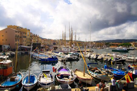 ST. TROPEZ, FRANCE - OCTOBER 2. 2019: View over boats and ships on promenade of mediterranean Harbour on cloudy day