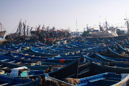 ESSAOUIRA, MOROCCO - SEPTEMBER 29. 2011: Countless blue fishing boats squeezed together in an utterly cramped harbor