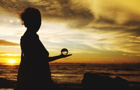 Silhouette of woman holding crystal ball against horizon in the evening sun on Ko Lanta, Thailand