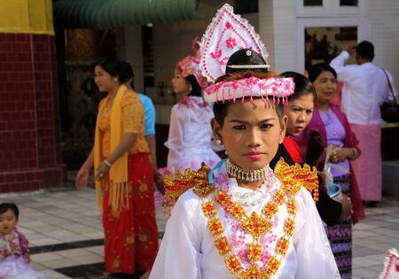MANDALAY, MYANMAR - DECEMBER 18. 2015: Novitiation (novitiate) ceremony (Shinbyu) for young Buddhist boy with make-up and lipstick at Maha Muni Pagoda