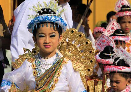 MANDALAY, MYANMAR - DECEMBER 18. 2015: Novitiation (novitiate) ceremony (Shinbyu) for young Buddhist boy with painted face carried on sedan at Maha Muni Pagoda
