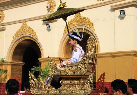 MANDALAY, MYANMAR - DECEMBER 18. 2015: Novitiation (novitiate) ceremony (Shinbyu) for young Buddhist boy on sedan chair at Maha Muni Pagoda
