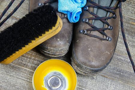 Cleaning brown dirty leather boots: Shoes, box with shoe wax, blue cloth and black brush on wood table