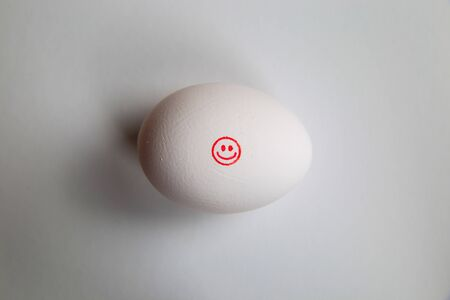 Take it easy and keep it simple concept: icon of red happy smiling face on isolated egg with with white background