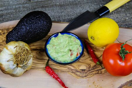 Ingredients for guacamole dip: avocado, citrus fruit, tomato, garlic, chillies, knife on wood table