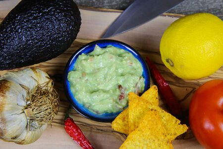 Ingredients for guacamole dip: avocado, citrus fruit, tomato, garlic, chillies, knife, tacos on wood table