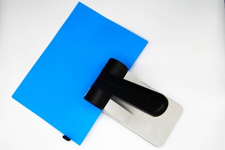 Top view close up of hole punch with blue paper sheet, white blank background