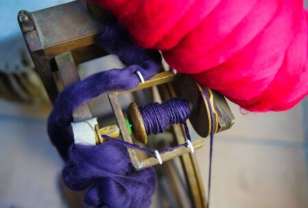 Close up of flyer with red and blue raw merino wool from old wooden spinning wheel