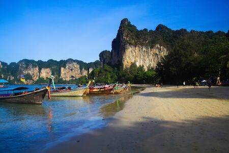View on secluded beach with high steep limestone cliffs and traditional thai long-tail boats - Railey, Krabi, Thailand Reklamní fotografie