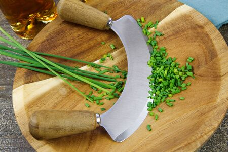 Preparation of herbs for meal: isolated brown wood cutting board with chef´s mincing knife, chopped green chives