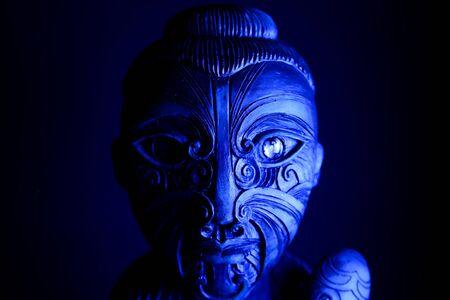 Studio shot of mystic hawaiian wood tattooed sculpture with mace illuminated by blue light