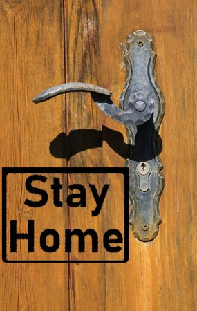 Corona virus covid-19 quarantine protection symbol concept: Text stay home on isolated old retro door with handle