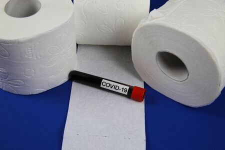 Mystery of stockpile objects and panic buying in corona virus crisis concept: Isolated white toilet paper rolls with covid-19 blood vial