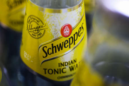 Viersen, Germany - May 9. 2020: Close up of yellow Schweppes Indian tonic water bottle in container (selective focus on center)