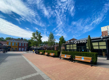 Roermond (designer outlet), Netherlands - May 19. 2020: View on square of exterior shopping mall in summer with blue sky