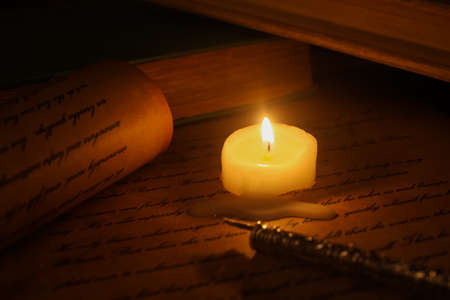 Viersen, Germany - May 22. 2020: View on isolated text on old yellow paper with ink pen and candle light (focus on pen tip, document is self made)