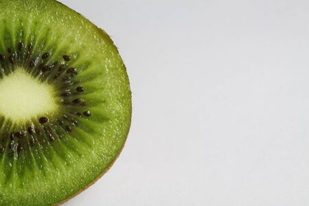 Macro close up of isolated half sliced fresh ripe green kiwifruit with white background and copy space for text Banque d'images
