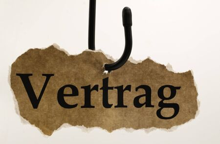 Luring customers and unfair adhesion contract concept: isolated piece of brown old scrap paper hanging on hook, white background (german word Vertrag means contract)