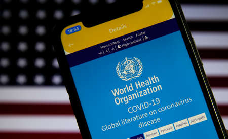 Viersen, Germany - July 8th 2020: Logo of world health organization (WHO) app on mobile phone screen. Blurred flag of USA background. Redactioneel