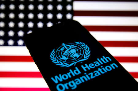 Viersen, Germany - July 8, 2020: Logo of world health organization (WHO) on mobile phone screen. Blurred flag of USA background. Redactioneel
