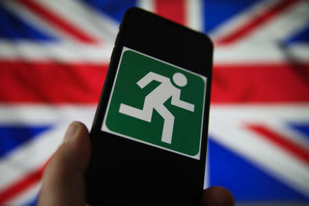 Viersen, Germany - July 9, 2020: View on isolated mobile phone screen with green emergency evacuation exit sign. Blurred union jack background. Redactioneel