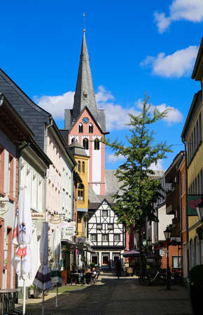 Kempen, Germany - July 9th 2020: View over pedestrian zone on white medieval timbered house with catholic church clock tower in summer with blue sky