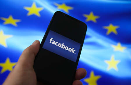 Viersen, Germany - July 9, 2020: View on mobile phone with facebook log lettering hold by hand. European union flag background. (selective focus on word book)