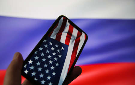 Viersen, Germany - July 9, 2020: View on hand holding mobile phone with USA flag. Flag of Russia background. (focus on upper part of american flag)