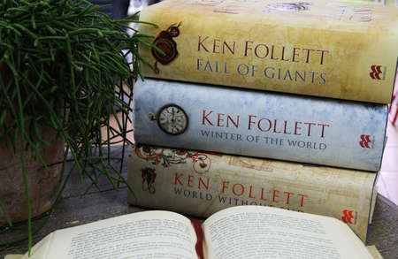 Viersen. Germany - July 9, 2020: View on wood table with open book, stack of Ken Follet novels books and green plant Redactioneel