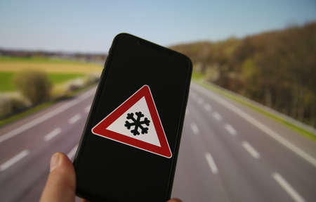 View on hand holding mobile phone with yellow triangle international black ice hazard symbol. Blurred highway background.