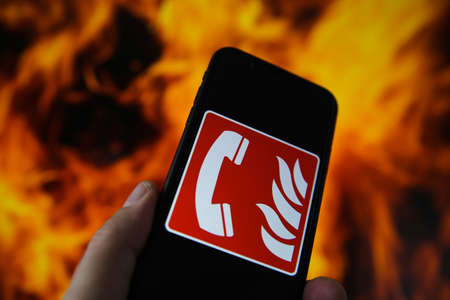 View on hand holding mobile phone with international fire emergency telephone symbol. Blurred fire flames background. (Selective focus on upper phone receiver)