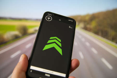Viersen, Germany - July 9th 2020: Closeup of hand holding mobile phone in car with radar warning speed check app.Blurred highway background.
