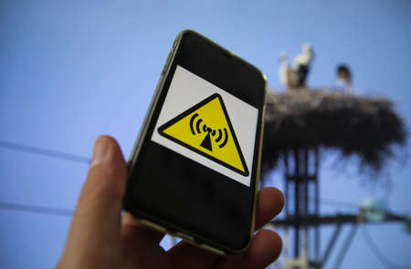 View on hand holding mobile phone with international radio frequency hazard sign against blue sky, power pole and electricity supply line with stork famyliy nest background. (focus on upper symbol) Redactioneel